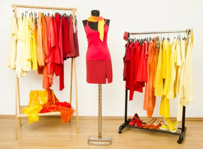 Wardrobe with yellow, orange and red clothes arranged on hangers.